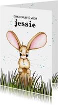 Kinderkaart konijn uitkijkend over het gras