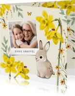 Een vrolijke lente paaskaart met bloemen, vlinders en konijn