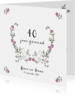 Jubileumkaart krans van blaadjes en rozen met twee duiven