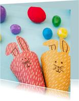 Kaart met twee paashazen en gekleurde eieren