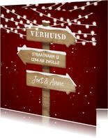 Kerst-verhuiskaart met lampjes, sneeuw en wegwijzerbord