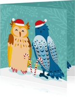 Kleurrijke kerstkaart met uilen in de sneeuw