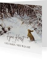 Lief kerstkonijn in winterbos onder besneeuwde takken