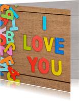 Liefde kaart met houten achtergrond en gekleurde letters