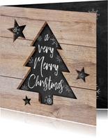 Moderne kerstkaart met hout, uitgesneden kerstboom en tekst