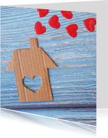 """""""Nieuw huis"""" kaart met kartonnen huis en rode harten"""
