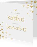 Papieren kerstkus door de brievenbus met hartjes