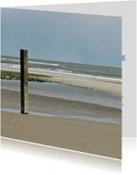 Strandpaal aan strand met zee 4k