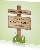 Verhuiskaart met wegwijzerbord en gras