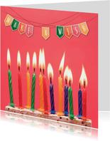 Verjaardagskaart met kleurrijke slinger en cake met kaarsen