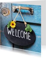 Welkom thuis kaart met krijtbord op een blauwe vintage deur