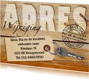 Adreswijziging met sleutel op houten achtergrond