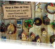 Een grappige verhuiskaart met vogelhuisjes op steigerhout