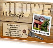 Leuk verhuisbericht met label, sleutel en foto op houtprint