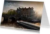Groeten uit Amsterdam met een foto van een grachtenpand