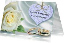 Trouwkaart met ringen, hart en witte roos op satijnprint