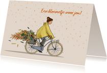 Verjaardagskaart vrouw in regenjas op fiets