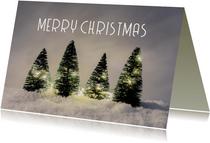 Winterse kerstkaart met kerstbomen in sneeuw