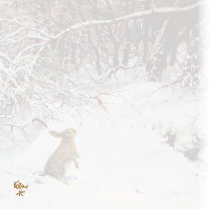 Lief kerstkonijn in winterbos onder besneeuwde takken 2